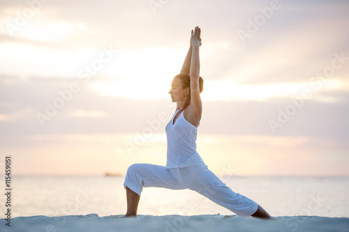 Caucasian woman practicing yoga at seashore Wallpaper Mural