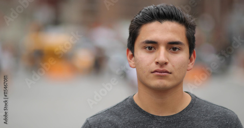 Fotografiet  Young latino man in city face portrait serious