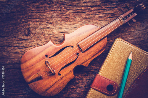 obraz PCV Violin and notebook with pencil on grunge dark wood background