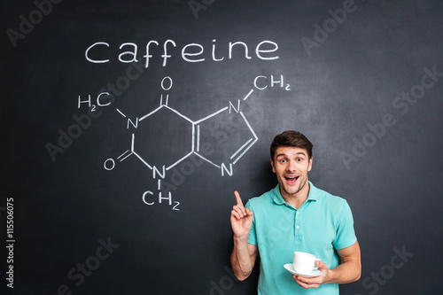 Fotografia, Obraz Smiling young man pointing on drawn caffeine molecule chemical structure