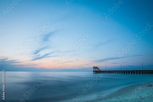 Fotobehang Aubergine Coastal coastline with sandy beach and pier at sunset.
