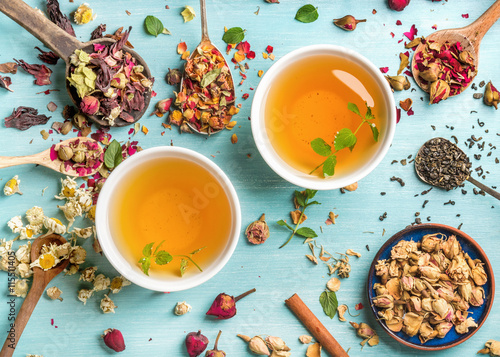 Poster Thee Two cups of healthy herbal tea with mint, cinnamon, dried rose and camomile flowers in spoons over blue background
