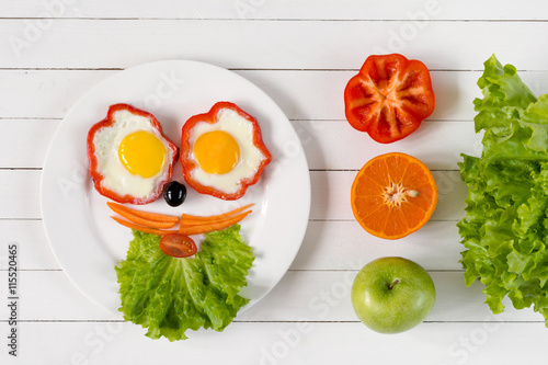 Healthy colorful breakfast concept. Smiling face on plate made with fresh healthy food. White wooden background