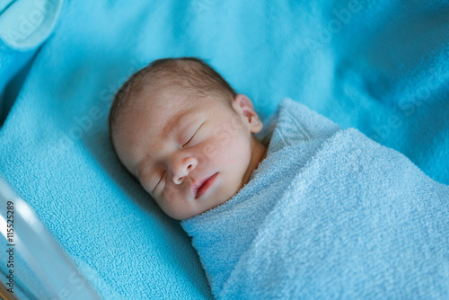 Newborn baby Asia  while sleeping covered with blue cloth