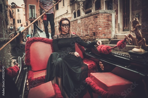 Beautiful woman in black dress with carnaval mask riding on gondola Fototapet