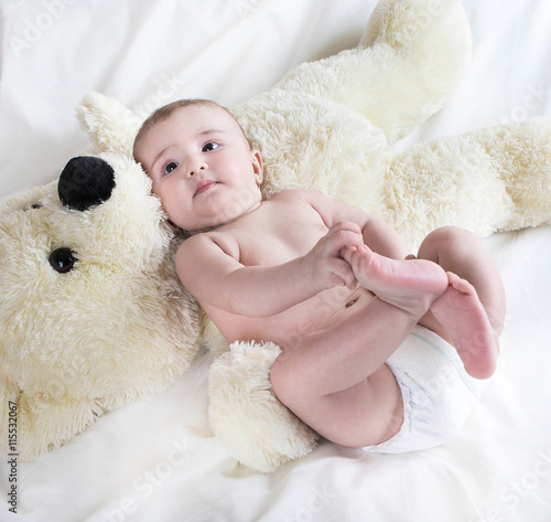 plakat .The baby is playing with bear in yellow