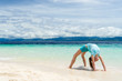 young slim teen girl do gymnastic exercise at white sand beach of tropical sea under blue sky