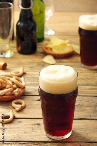 Fotografia  bicchiere di  birra scura su sfondo tavolo di legno rustico