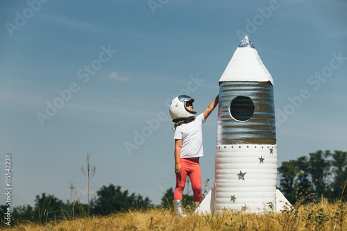 Fotografie, Obraz  Happy child girl dressed in an astronaut costume playing with hand made rocket