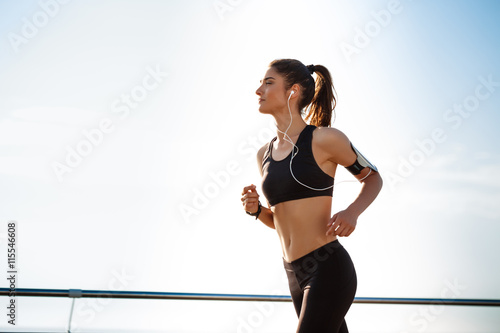 Picture of young attractive fitness girl jogging Fototapete