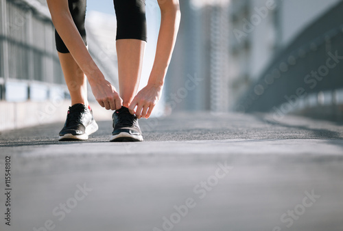 Fotografie, Obraz  Getting ready for a run. Female runner tying her shoe.