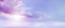Romantic Lilac Sky Scape - Beautiful Wide Lilac And Pink Clouds Lue Sky And Cloud Scape With A Burst Of Sunlight Emerging From Under The Cloud Base With Plenty Of Copy Space