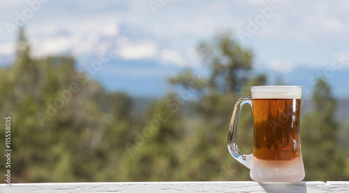 Photo  Cold beer in a chilled mug outside
