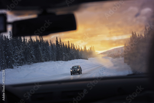 Sweden, Lapland, Hemavan, Car seen through windshield driving dirt road covered with snow at sunset
