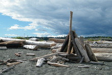 Driftwood Teepee On A Sandy Beach With Clouds Blowing Away