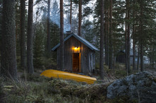 Yellow Rowboat In Front Of Wooden Cottage In Forest