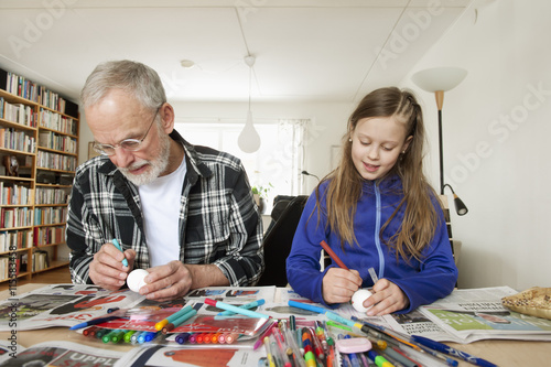 Sweden, Girl (10-11) with grandfather coloring eggs in living room