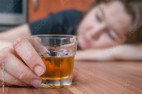 Fotografía  Alcoholic woman is sleeping on table. Glass with alcohol in hand.