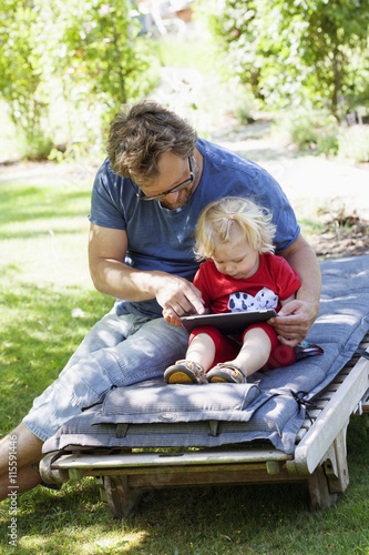 Sweden, Skane, Mossby, Daughter with father sitting on deckchair and using tablet pc