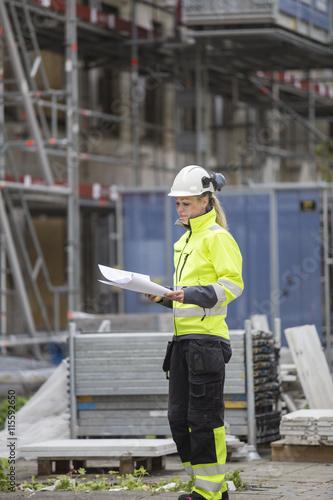 Sweden, Vastergotland, Construction worker looking at blueprints