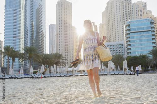United Arab Emirates, Dubai, Woman walking on sandy beach Poster
