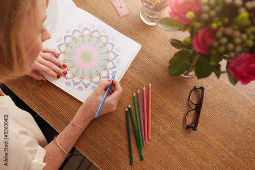 Female drawing in adult coloring book at home