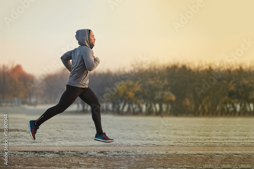 Poster Jogging Young athletic man running at park during cold autumn morning