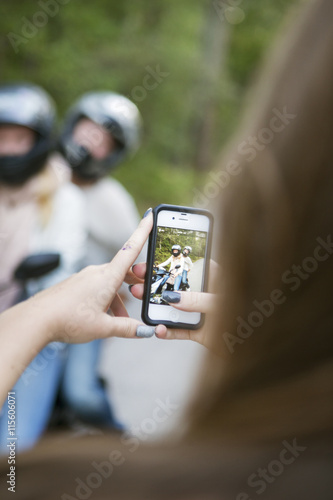 Sweden, Sodermanland, Nacka, Girl (14-15) taking photo of her friends on scooter with smartphone