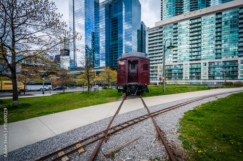 Railroad car at Roundhouse Park and modern buildings in