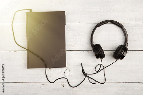 Fotografía  Audio book concept with black book and headphones on white wood