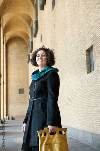 Sweden, Vastra Gotaland, Gothenburg, Portrait of smiling woman holding yellow handbag