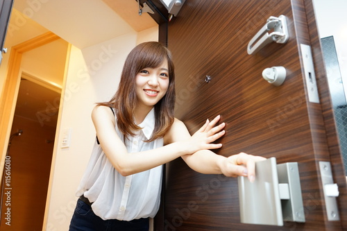 Fotografia, Obraz  Young Japanese woman opening door for delivery service 一人暮らしの自宅玄関のドアを開ける若い女性