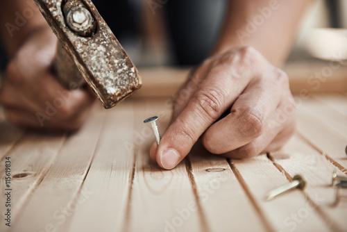 Obraz na plátne Close-up of handyman hammering a nail in wooden board