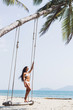 Beautiful thin woman swinging on a swing on paradise beach with