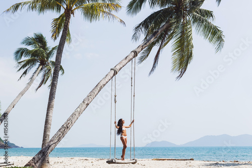 Photo  Beautiful thin woman swinging on a swing on paradise beach with