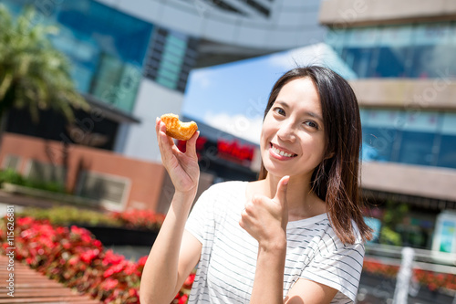 Woman having egg tart in Hong Kong Poster