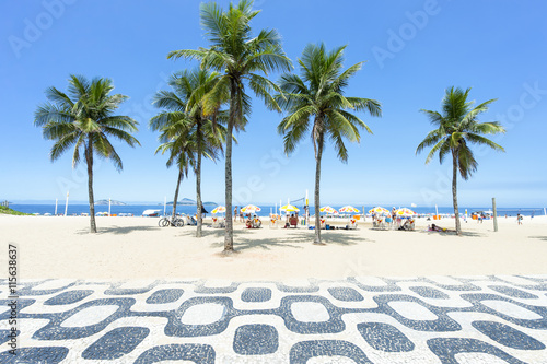 Classic empty view of the Ipanema Beach boardwalk with palm trees and blue sky a Canvas Print