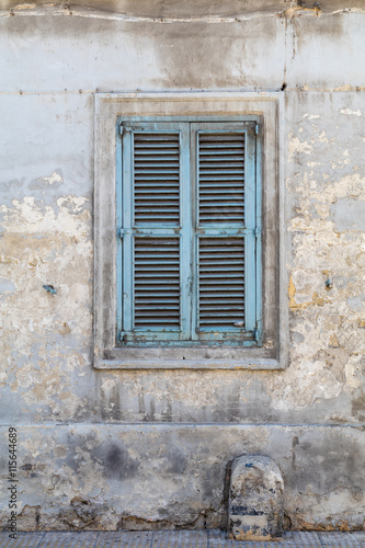 Photo  Weathered and Ancient Maltese shuttered window , blue