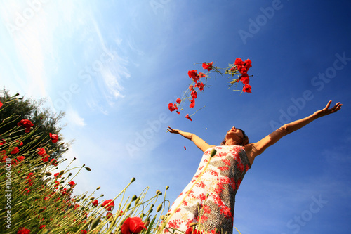 Photo femme joyeuse qui lance des coquelicots en l'air