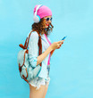Pretty woman listens to music in headphones using smartphone ove
