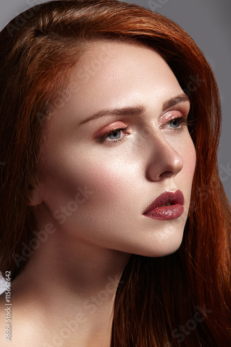 Beautiful ginger young woman with luxury hair style and fashion gloss makeup. Beauty portrait of sexy model with red hair. Long soft shiny hairstyle.