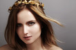 Beautiful young woman with gold crown, flying light color hair. Beauty portrait with clean skin, glamour fashion makeup. Accessories, make up, hairstyle. Haircare, make-up