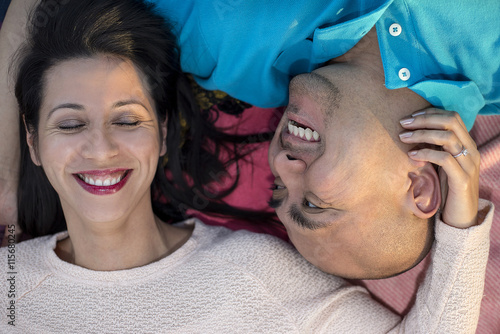 Fotografie, Obraz  Engaged latino couple laying on a park looking carefree happy and in love