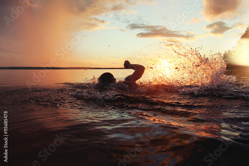 Canvas Print Athletic man is trained to swim in a lake at sunset