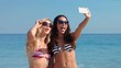 Video of happy pretty friends taking a selfie at the beach