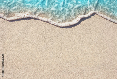 Door stickers Water Soft ocean wave on the sandy beach, background.