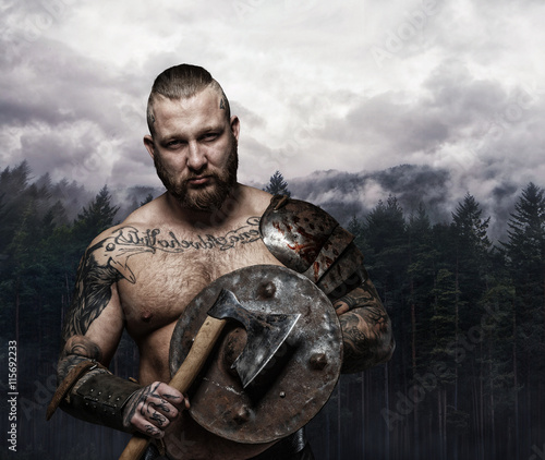 Photo  Viking holding wooden shield and axe.