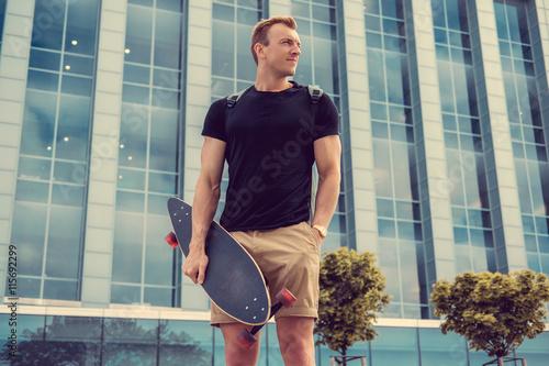 obraz PCV Casual urban male holding longboard.