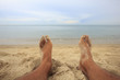 man feet close-up relaxing on beach when cloudy and rainy day ; disappointed holiday concept