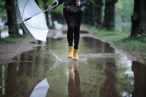 Obraz na płótnie feet in rubber boots rain puddle city